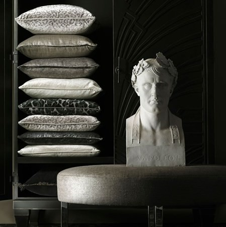 Tiesto - Silver - A black cabinet stacked with nine luxurious black and silver cushions, beside a grey footstool and a classical bust