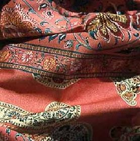 Udaipur - Red - Folds of salmon pink coloured 100% cotton fabric patterned with ornate, multicoloured patterns, florals & paisley shapes