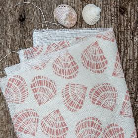 Cockle Shells - Coral Pink - Two shells beside white linen and cotton blend fabric printed with a simple sea shell design in a light shade o