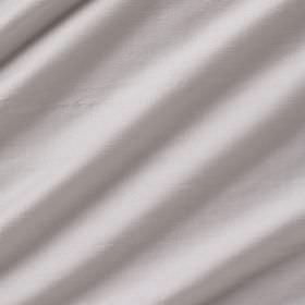 Astor - Luna - 100% polyester fabric arranged in folds in a very pale silver-white colour