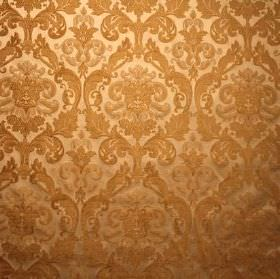 Hamilton - Gold - Dark and light shades of gold making up a repeated, ornate pattern on fabric blended from viscose and polyester