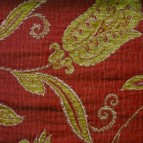 Bronte Emily - Terracotta - Ornate lime green florals patterning terracotta coloured fabric made from polyester and acrylic
