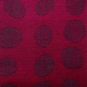Darcey Pebble - Ruby - Very dark reddish grey dots and ovals in irregular shapes on a burgundy coloured fabric containing cotton and polyest