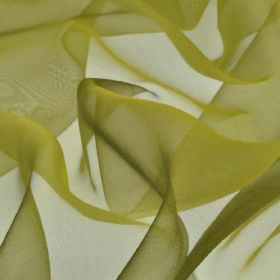 Gavotte - Green (36) - A slight translucent finish on 100% Trevira CS fabric in an olive green-gold colour