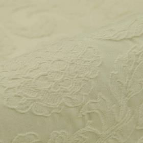 Musca - White - Ivory coloured cotton and polyester blend fabric with a subtle floral and leaf pattern which is raised and embroidered