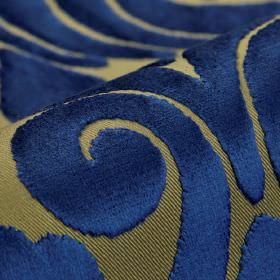 Aries - Blue Cream - Fabric made from green-grey polyester and viscose behind a subtly textured swirl pattern in rich, luxurious navy blue