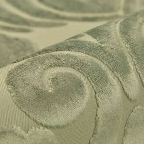Aries - Light Grey - A soft, velvety texture covering a large swirl pattern on silvery-grey coloured fabric made from polyester and viscose