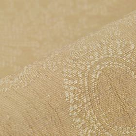 Tournelle - Beige - Beige polyester and viscose blend fabric behind a cream coloured embroidered design of circles and ornate flowers