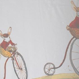 Racing - Multi Coloured - White 100% cotton fabric printed with penny farthings being ridden by animals wearing clothes in red, grey and yel