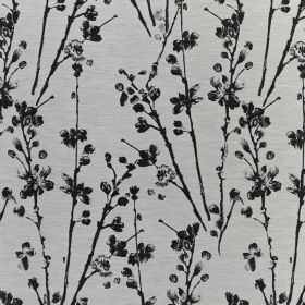 Meadow - Chrome - A light grey background behind black stalks and petals printed on fabric containing a mixture of polyester and cotton