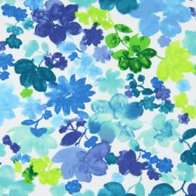 Cassandra - Indigo - Flowers of lime green, bright green and different shades of blue which appear to have been painted on white cotton fabric