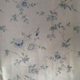 Rupali - Faded Indigo - Flowers in shades of blue and grey as a fairly widely spaced floral pattern on cream coloured 100% linen fabric