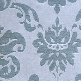 Sojana - Blue Crystal - A solid dusky blue simple, stylised floral and swirl pattern printed on a light blue 100% Trevira CS fabric backgrou