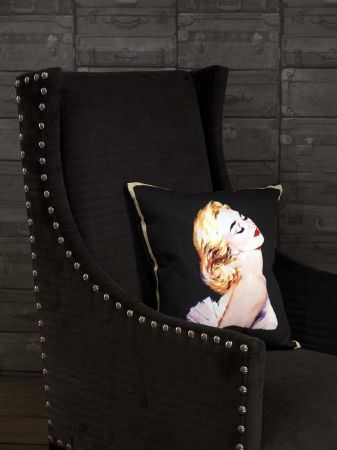 Andrew Martin -  Archive Fabric Collection - Modern studded upholstered armchair in black with a black cushion that has gold borders and a picture of a woman