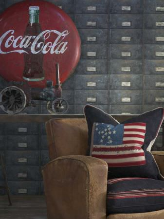Andrew Martin -  Archive Fabric Collection - Simple upholstered armchair in brown and a decorative cushion decorated with the American flag