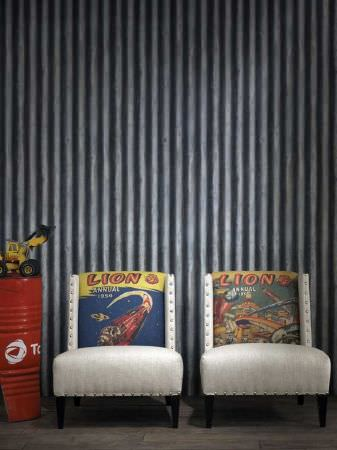 Andrew Martin -  Archive Fabric Collection - Two upholstered white armchairs with black legs decorated with images from Lion Annual comics