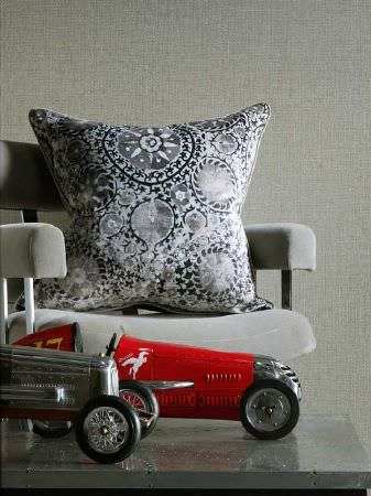 Andrew Martin -  Carlotta Fabric Collection - A scatter cushion with an ornate grey and black pattern, on a light grey fabric armchair, beside toy vintage racing cars