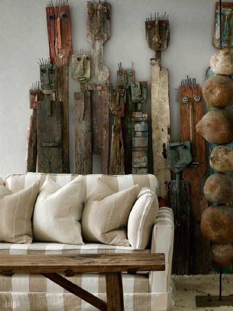 Andrew Martin -  Carlotta Fabric Collection - A series of tribal human sculptures behind a cream and caramel striped sofa with matching cushions and a wooden table