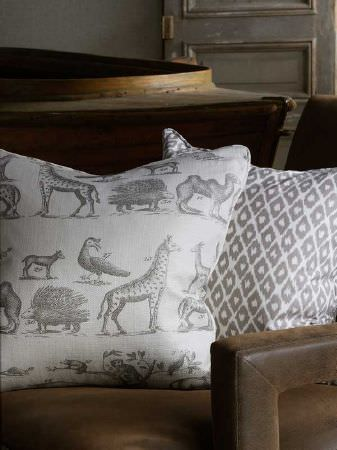 Andrew Martin -  Carlotta Fabric Collection - A plain wooden boat beside a dark brown padded armchair with diamond and African animal print cushions in grey and white