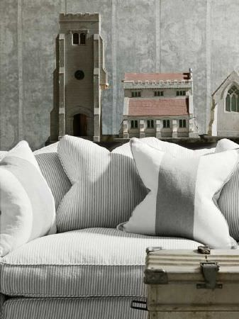 Andrew Martin -  Carlotta Fabric Collection - Grey and white striped cushions on a pinstripe patterned sofa, with patterned wallpaper and church and building sculptures