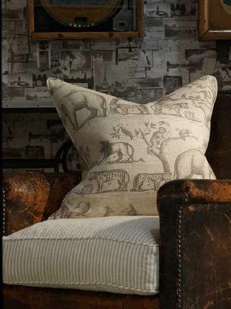 Andrew Martin -  Carlotta Fabric Collection - A distressed brown leather armchair with pinstripe seat and animal print scatter cushions, and patterned wallpaper
