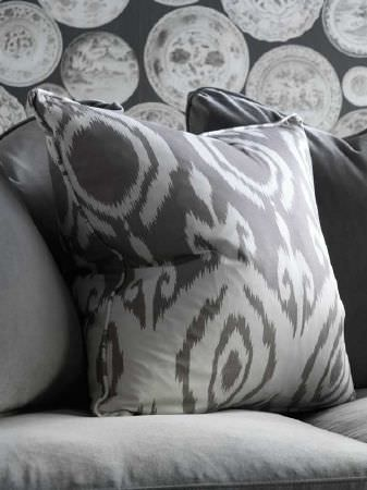 Andrew Martin -  Carlotta Fabric Collection - Plain and abstract patterned cushions, a sofa and circular patterned wallpaper, all in black and various shades of grey