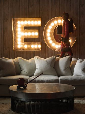 Andrew Martin -  Clarendon Fabric Collection - A diver scuplture, large lightbulb letters, a large plain white sofa, and a round wood and metal coffee table