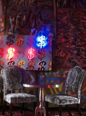 Andrew Martin -  Clarendon Fabric Collection - A dollar sign painting lit with neon lights, with a round metallic silver table and two ornately patterned grey chairs