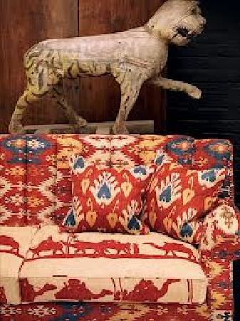 Andrew Martin -  Discovery Plain Fabric Collection - Sofa with dark red and blue Aztec-like pattern with seat cushions in pale sandy colour, depicting dark red camel-like creatures.
