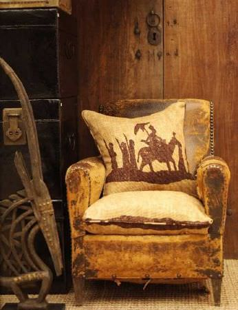 Andrew Martin -  Discovery Plain Fabric Collection - Armchair in velvet-like mottled golden beige with gold-beige cushion depicting rider and horse with attendant figures in mid-brown.