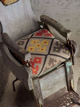 Andrew Martin -  Inventor Fabric Collection - Seat cushion with beige tapestry-effect background and bold geometric style flowers in yellow and orange with dark diamond shape markings.