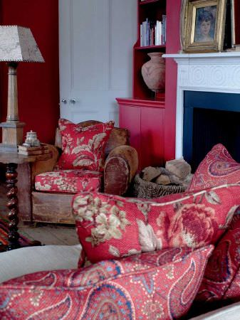 Andrew Martin -  Inventor Fabric Collection - Armchair in dusty pink velvet with cushions in deep pink with bold swirling flowers and foliage. One pink Paisley-effect cushion.