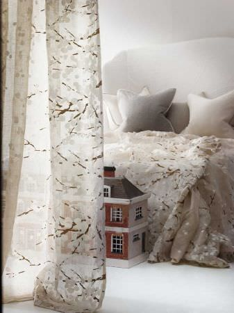 Andrew Martin -  Lost and Found Fabric Collection - Bedding and sheer curtains covered with a white and brown cherry blossom pattern, with plain grey and white cushions