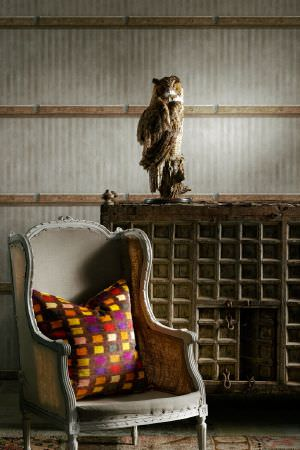 Andrew Martin -  Lost and Found Fabric Collection - A stuffed owl statue beside a light grey coloured wood and fabric sofa, with an orange, yellow, purple and white cushion