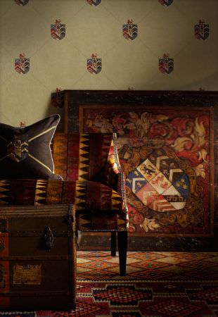 Andrew Martin -  Lost and Found Fabric Collection - Crest and tribal themed rugs, sofa upholstery and cushion, all in dark red, brown and cream shades, with a wooden chest