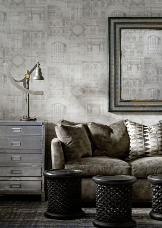 Andrew Martin -  Lost and Found Fabric Collection - Building print wallpaper, a plain sofa, patterned cushion, metal chest of drawers, and side tables, all in shades of grey