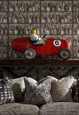 Andrew Martin -  Lost and Found Fabric Collection - A toy vintage red racing car on a wooden topped metal table behind a light grey sofa with plain and patterned cushions