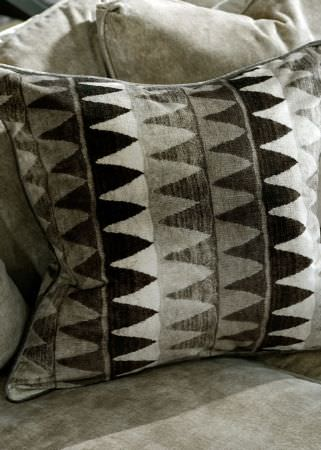 Andrew Martin -  Lost and Found Fabric Collection - Shades of black and grey making up a tessellated triangle pattern on a cushion, with plain light grey cushions and a sofa