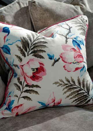 Andrew Martin -  Lost and Found Fabric Collection - Plain light grey sofa and cushions with a floral patterned square scatter cushion, made in white, pink, blue and grey