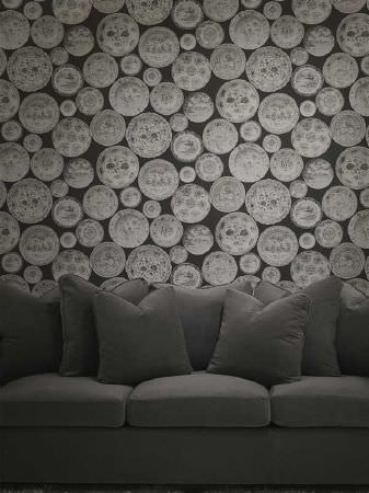 Andrew Martin -  Pelham Fabric Collection - Black and light grey circle shaped Classical themed wallpaper, behind a large, padded, plain charcoal coloured sofa