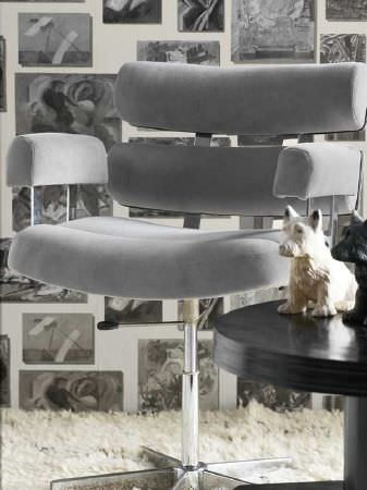 Andrew Martin -  Pelham Fabric Collection - Contemporary light grey fabric and metal swivel chair, with a round black table, a fluffy white rug, and patterned wallpaper