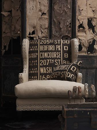 Andrew Martin -  Spectator Fabric Collection - Armchair in light mushroom velvet-type fabric with studded edges and dark brown back with lighter lettering. Matching cushion.