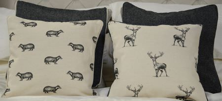 Art of the Loom -  Art of the Loom Fabric Collection - A set featuring modern black cushions and white cushions featuring a pattern of racoons and deer