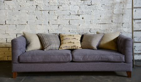 Art of the Loom -  Art of the Loom Fabric Collection - Plain dark purple upholstered sofa covered with a set of cushions with different decorative patterns