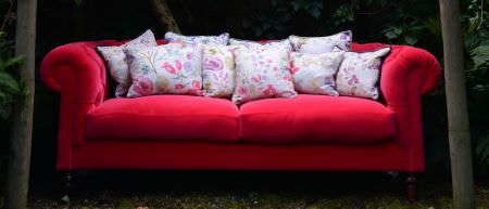 Art of the Loom -  Art of the Loom Fabric Collection - Vibrant red sofa covered with a collection of white cushions featuring vibrant floral decorations