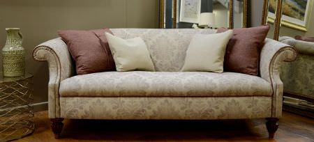 Art of the Loom -  Art of the Loom Fabric Collection - Beige couch featuring grand floral pattern and a set of plain cushions in white and dark red