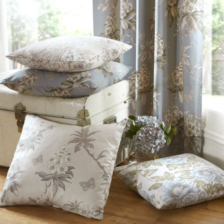 Ashley Wilde -  Avebury Fabric Collection - Light blue transparent curtains with a floral design and a collection of white and blue cushions with matching designs