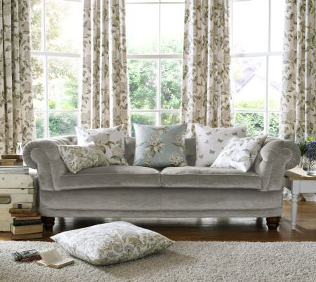 Ashley Wilde -  Avebury Fabric Collection - Light beige curtains with modern floral design and a collection of white and blue cushions with floral designs