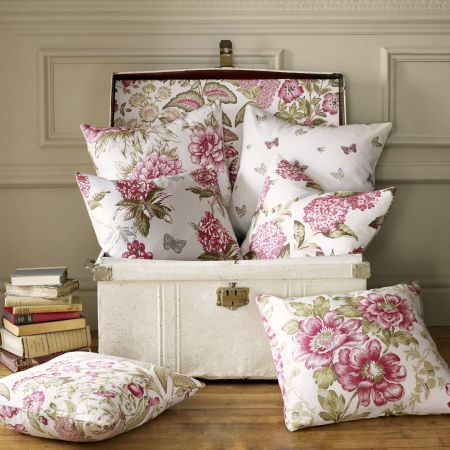 Ashley Wilde -  Avebury Fabric Collection - A collection of white cushions featuring vibrant patterns of flowers or colourful butterfly pattern