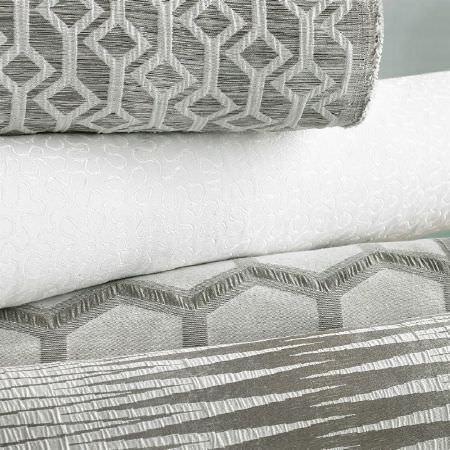 Ashley Wilde -  Axel Fabric Collection - Subtly patterned white fabric with three rolls of fabric featuring different patterns in light and dark shades of grey